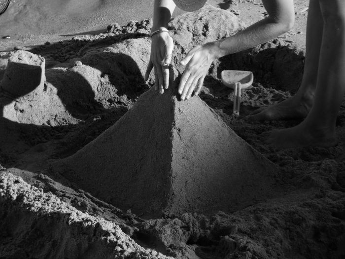 Cropped image of person making sand pyramid at beach