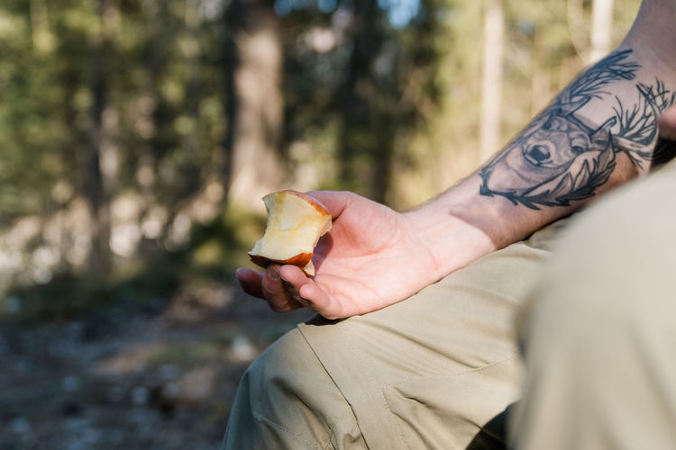 Close-up of inked male arm holding an apple