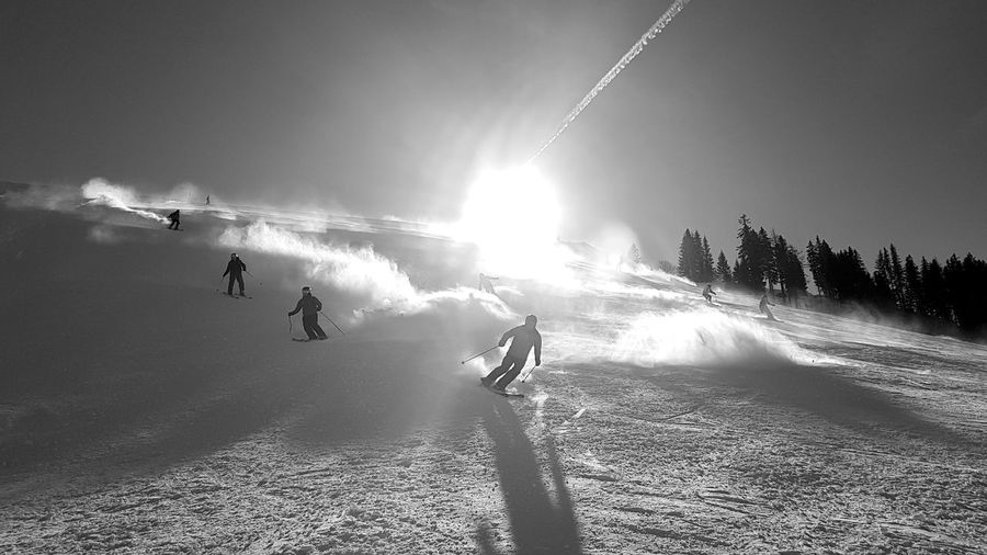 People skiing on field against sky during winter