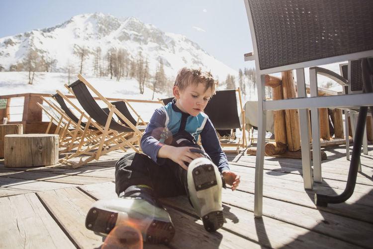 Full length of boy sitting on mountain