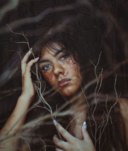 Close-up portrait of messy young woman by dead plants