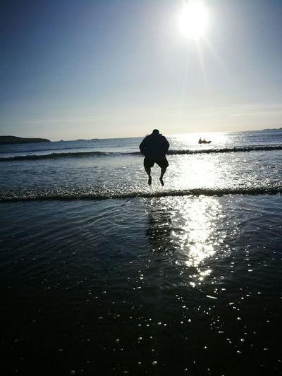 Silhouette man walking on beach against clear sky