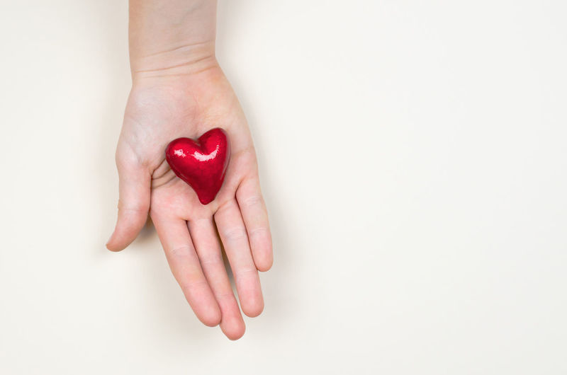 Close-up of woman hand holding heart shape over white background
