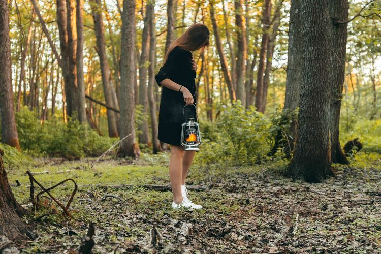 Girl in black skirt with oil lamp walking on the forest at the evening. Awesome mood. Adult Beautiful Woman Day Forest Full Length Growth Hairstyle Land Leisure Activity Lifestyles Nature One Person Outdoors Plant Real People Tree Tree Trunk Trunk Women WoodLand Young Adult Young Women