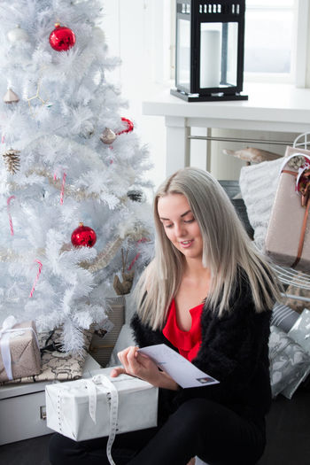 Christmas Smiling Happiness Young Women One Person Celebration Emotion Women christmas tree Tree Indoors  Blond Hair Hair Sitting Lifestyles Adult Holiday Real People Christmas Ornament Hairstyle Beautiful Woman Positive Emotion Nordic Countries Happiness Merry Christmas Moments Of Happiness