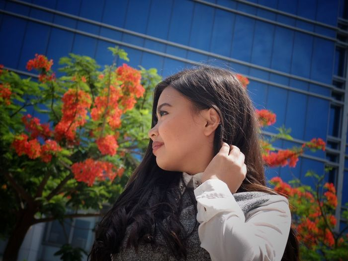 Low angle view of woman with hand in hair looking away against blue building