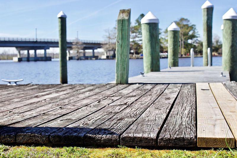 Wooden pier over river against sky