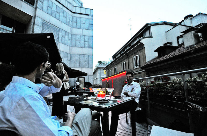 People sitting on table in city against clear sky