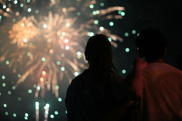 Low angle view of man and woman looking at firework display