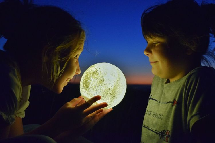 Side view of sisters playing with illuminated ball against sky during sunset