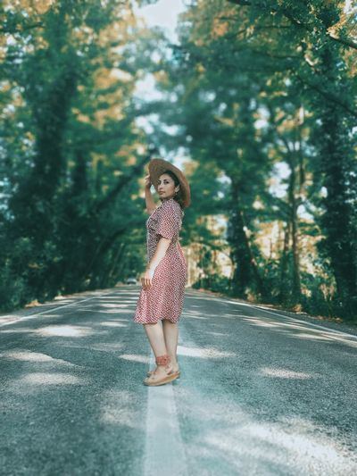 Full length portrait of woman standing on road