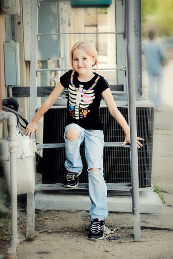 Portrait of young girl smiling on metal steps