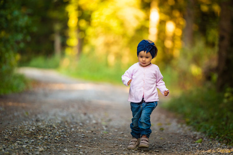 Full length of baby girl walking on dirt road amidst forest