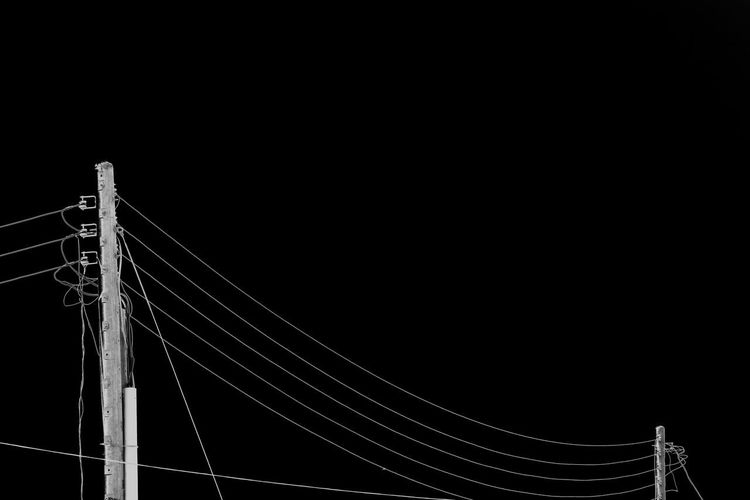 Low angle view of suspension bridge against sky at night