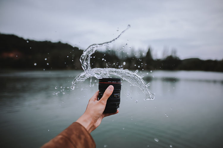 Man holding water splashing on lake