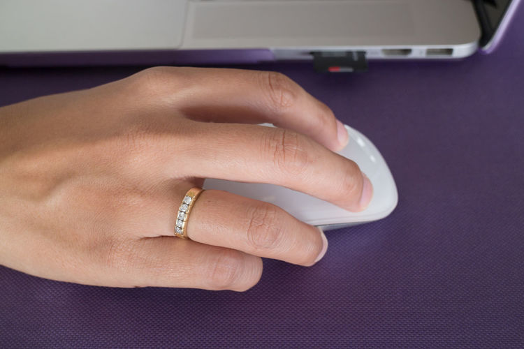 Cropped Hand Of Woman Using Computer Mouse On Tablecloth
