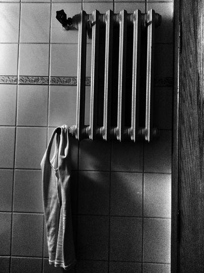 Tank top hanging on radiator in bathroom