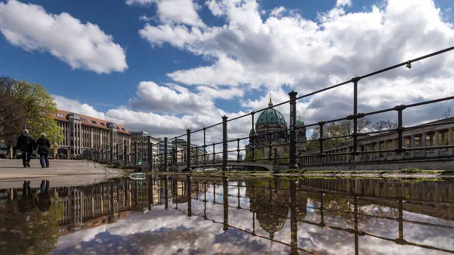 Reflection of berlin cathedral on puddle against sky