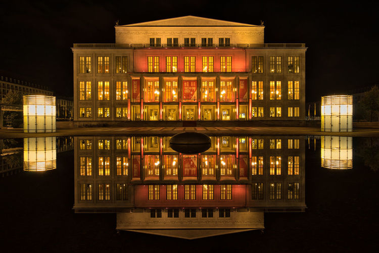 Reflection of illuminated building in river at night