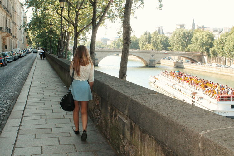 Rear view of woman walking on footpath by seine river
