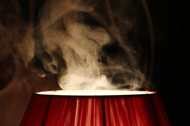 Close-Up Of Smoke Over Illuminated Lamp