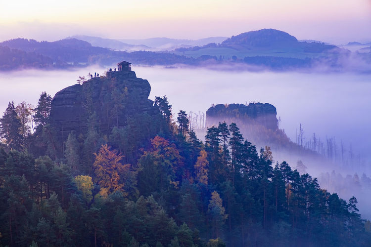 Beautiful orange and red autumn forest in mist. high rocky peaks above white mist