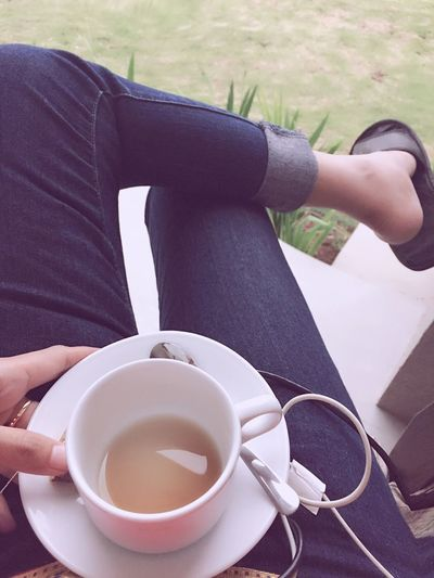 Low section of woman having coffee while sitting outdoors