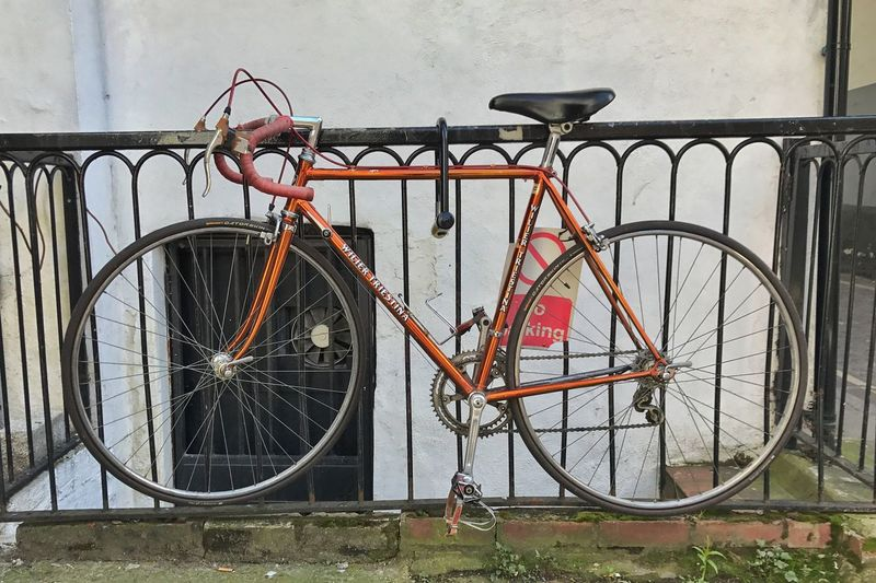 Bicycle parked by railing against building