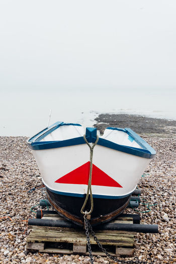 Boat Ocean Seascape Sea Beach Stationary Parked Nautical Vessel Mode Of Transportation Water Moored Transportation Land Sky Nature Day No People Outdoors Scenics - Nature Tranquility Sand Tranquil Scene Copy Space Rowboat Pebble Scenics Calm Sailboat Sailing Fishing Boat