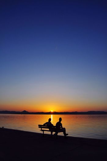 Silhouette People Sitting On Bench By Sea Against Sky