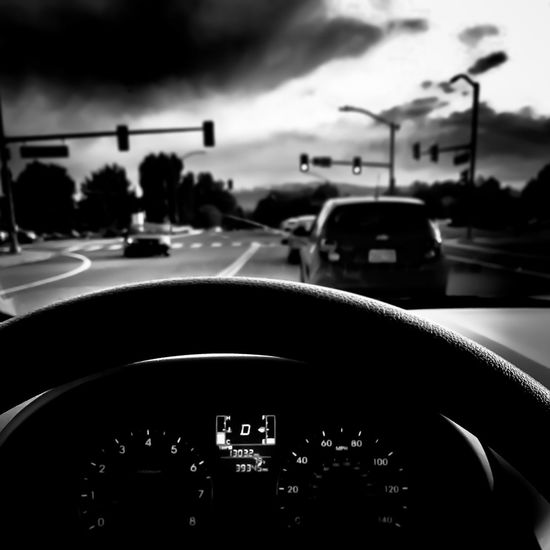 From the steering wheel point of view at a red light. Transportation Car Vehicle Interior Car Interior Land Vehicle Dashboard Mode Of Transport Windshield Steering Wheel Road Car Point Of View Sky Speedometer Day No People Close-up Outdoors