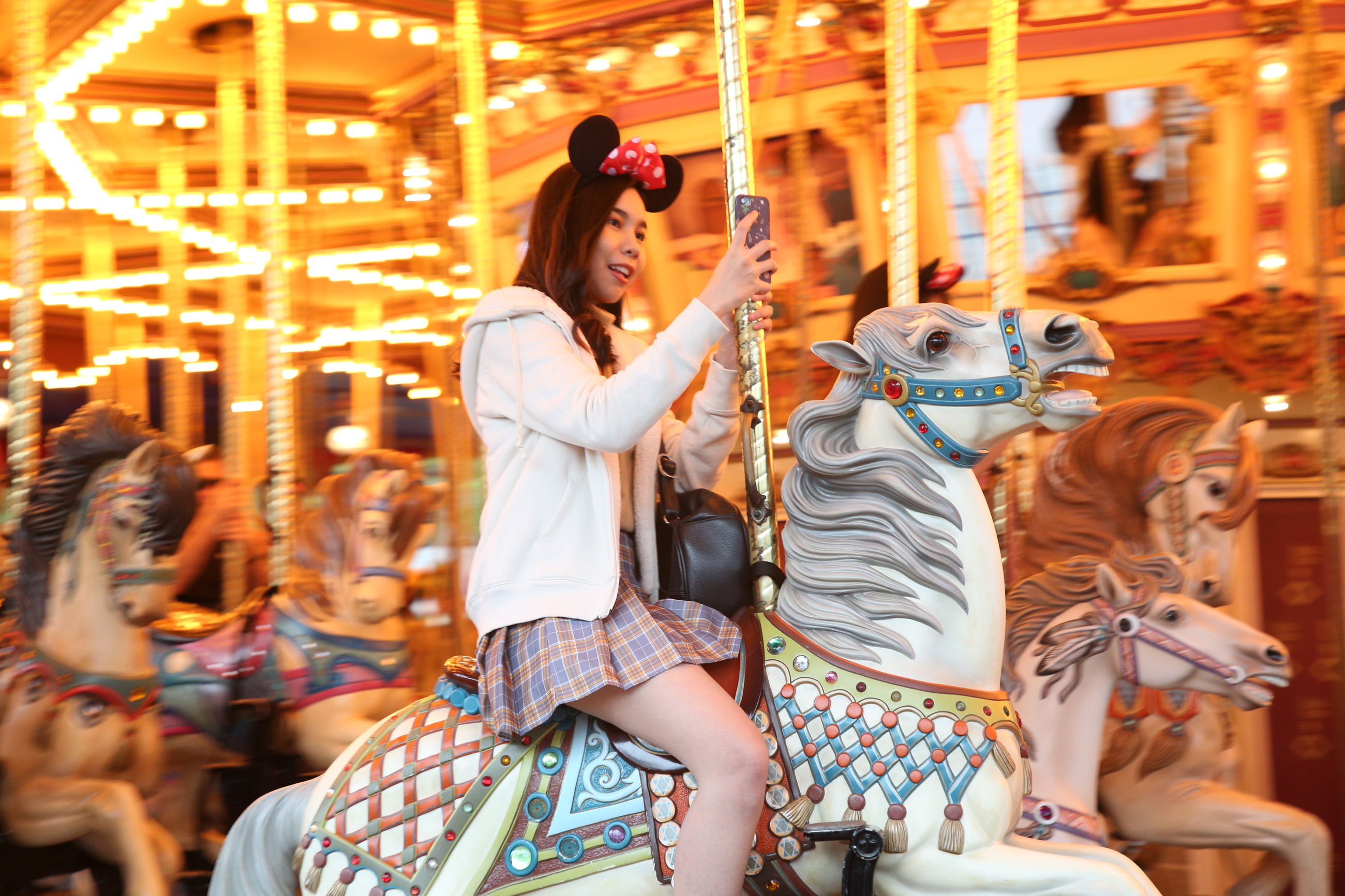 amusement park, amusement park ride, carousel, women, leisure activity, real people, lifestyles, illuminated, representation, arts culture and entertainment, adult, people, enjoyment, group of people, three quarter length, motion, casual clothing, livestock, outdoors