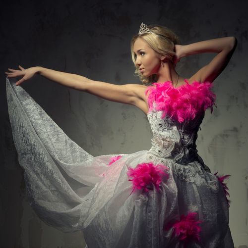 Beautiful young woman in pink and white wedding dress dancing against wall