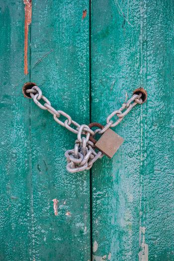 Close-Up Of Padlock In Chain Hanging On Door