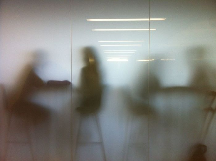 People Sitting On Chairs In Cafe Seen Through Glass