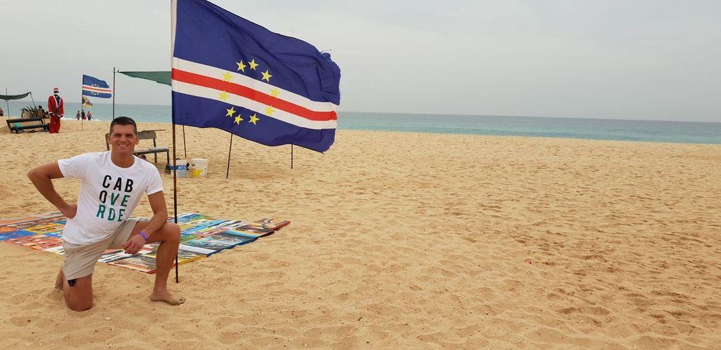 Men flag on beach against sky