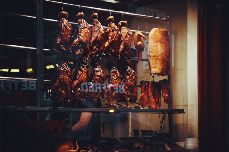 Storefront view of hanging ducks in a restsurant.