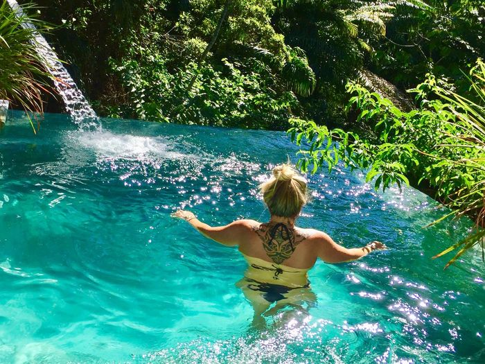 Rear view of woman swimming in infinity pool