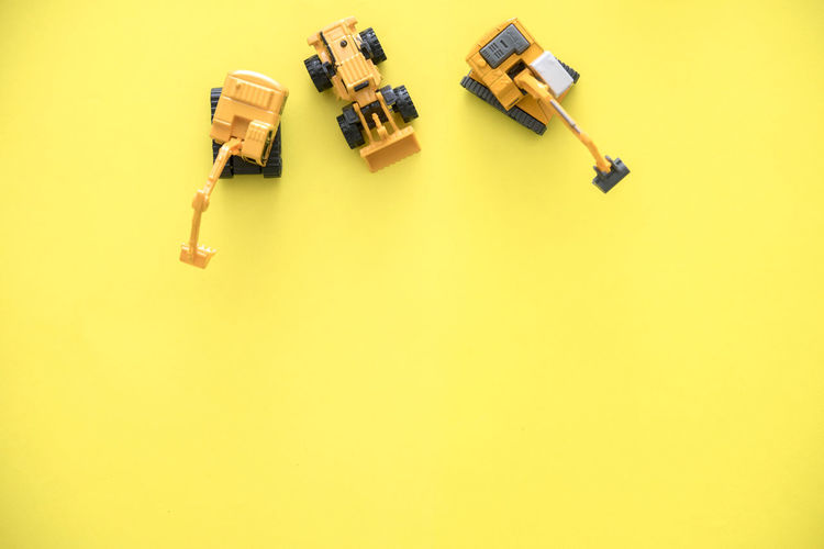 Directly above shot toy vehicles on yellow background