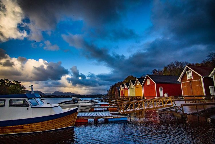 Boats moored on sea by houses against sky