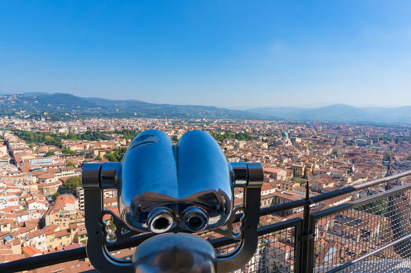 Coin-Operated Binoculars On Cityscape Against Blue Sky In City