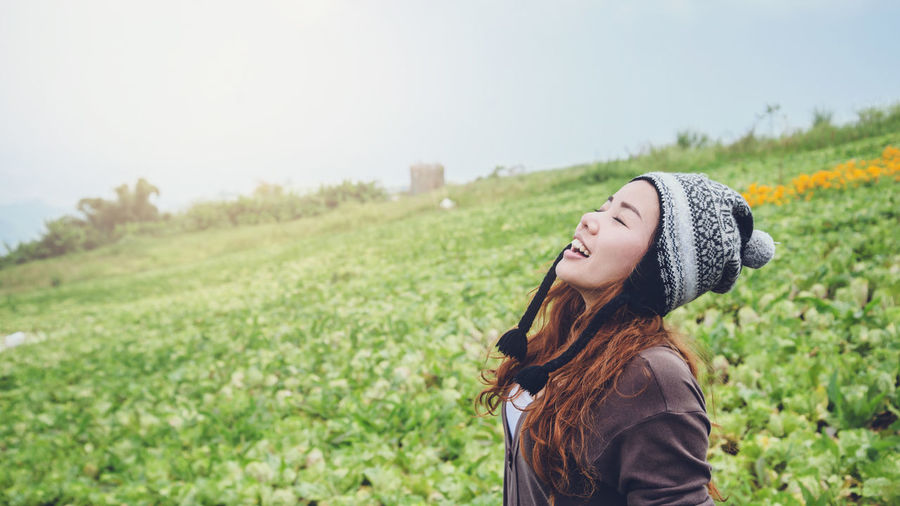 Woman with eyes closed standing on agricultural field