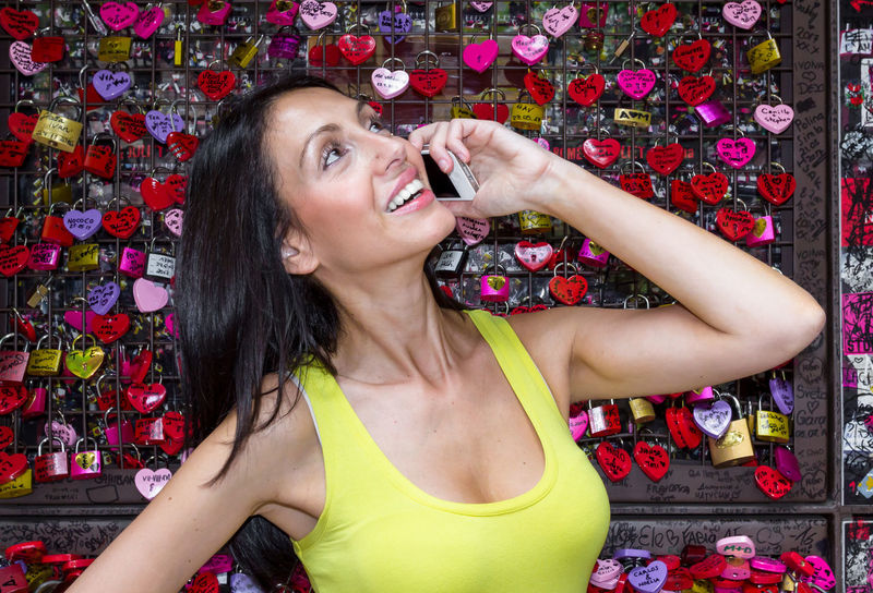 Smiling beautiful woman in love talking on the mobile phone. In the background many padlocks in the shape of a heart. Beautiful Fun Hair Happiness Happy Holiday Lifestyle Locks Love Attraction Attractive Background Beauty Call Day Female Girl Giulietta Hearts House Italy Juliet  Key Landmark Lock