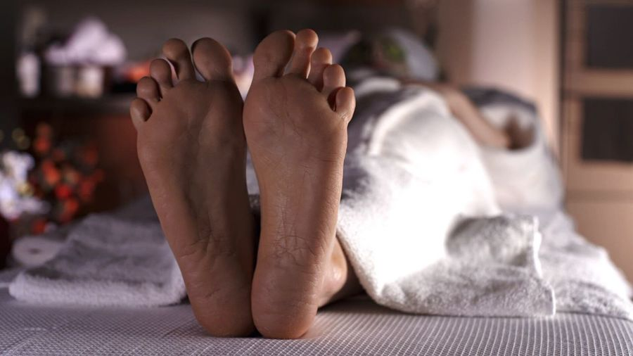 Woman Lying On Bed With Focus On Her Feet At Spa
