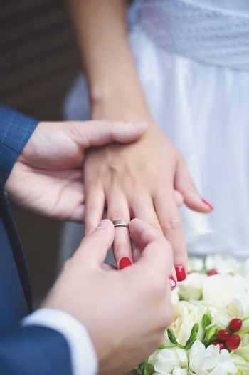 Cropped Image Of Bridegroom Putting Ring In Hand Of Bride