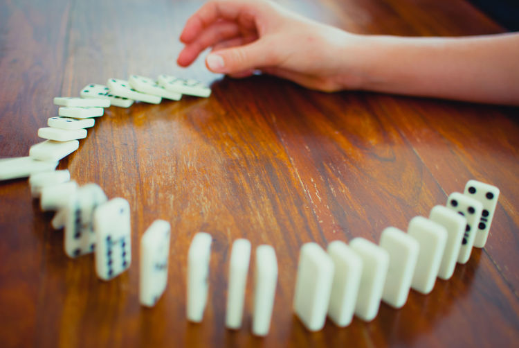 Close-up of human hand pushing first domino in a row