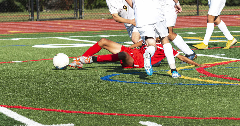 Low section of men playing soccer on field