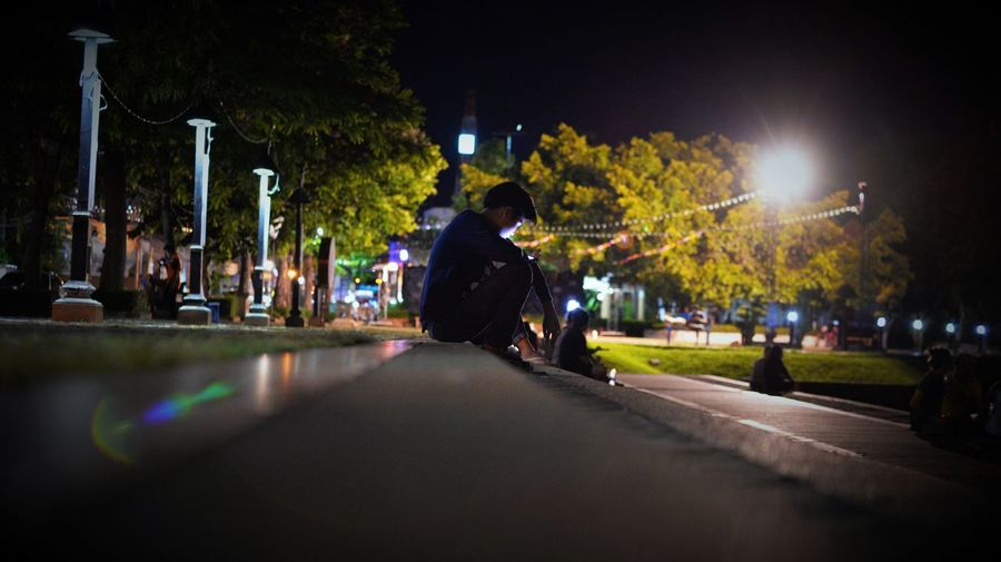 summer time city life Thailand Summer In The City Thailand Summer Adult Architecture City City Life Illuminated Nature Night One Person Outdoors Plant Rear View Road Sitting Street Street Light Summer Summer Time  Transportation Tree Capture Tomorrow