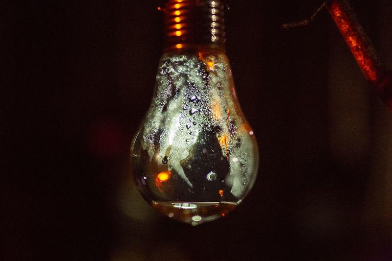 Close-up of illuminated glass hanging against black background