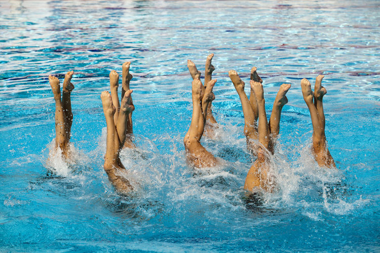 People Performing Synchronized Swimming In Pool